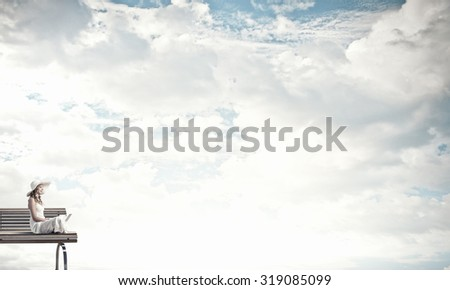 Young lady sitting on bench and using laptop - stock photo