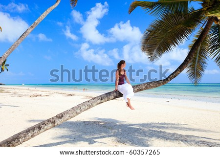 Young lady sitting on palm tree at tropical beach - stock photo