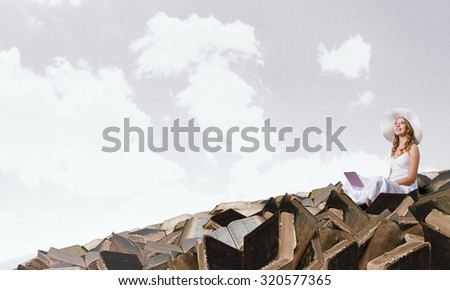 Young lady sitting on pile of books with laptop - stock photo