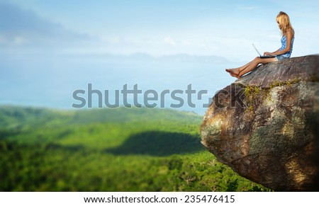 Young lady sitting on top of the mountain with laptop. Edges are blurred - stock photo