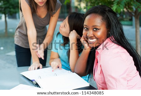 Young lady smiling at camera while friends study in background - stock photo