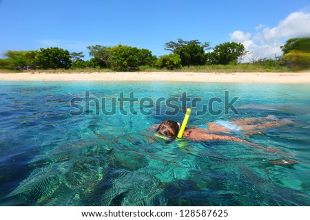 Young lady snorkeling in a tropical sea - stock photo