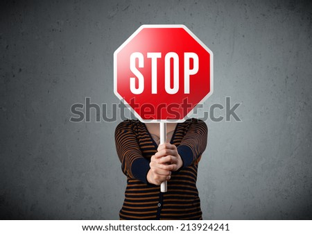 Young lady standing and holding a stop sign in front of her head - stock photo
