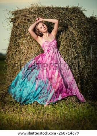 Young lady standing in evening field. Beautiful woman posing at the old rural farm location. Outdoor summer portrait of pretty fashion style woman in colored dress over haystack. Beautiful slim girl - stock photo