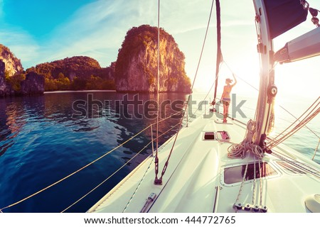 Young lady standing on the bow of yacht and looking to the rocky island at sunrise - stock photo