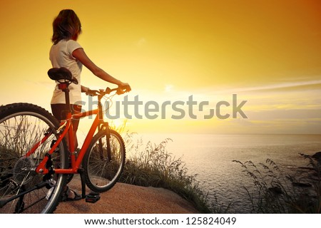 Young lady standing on top of a hill with bicycle and enjoying the sunset over sea - stock photo