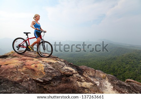 Young lady standing on top of a mountain with bicycle