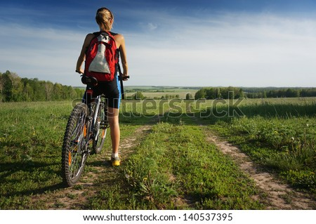 Young lady standing with bicycle on a rural road in a meadow - stock photo