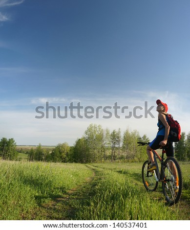 Young lady standing with bicycle on a rural road in a meadow