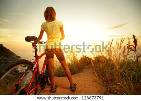 Young lady standing with bicycle on a sea coast and enjoying sunset - stock photo
