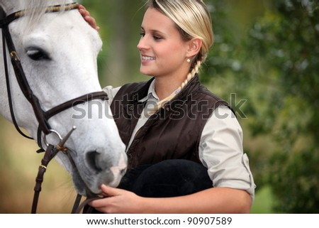 Young lady stroking her horse