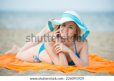 Young lady sunbathing on a beach. Beautiful woman posing at the summer sand beach. Outdoor summer portrait Ocean sea coast. Beautiful fit tan girl. Sexy slim model caucasian ethnicity outdoors. - stock photo