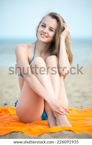 Young lady sunbathing on a beach. Beautiful woman posing at the summer sand beach. Outdoor summer portrait of pretty sport style woman in blue bikini. Ocean sea coast. Beautiful fit tan girl.  - stock photo