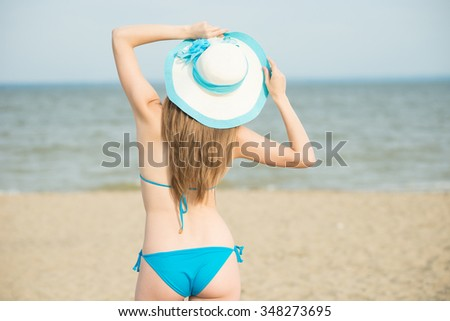 Young lady sunbathing on a beach. Beautiful woman posing at the summer sand beach. Outdoor summer portrait of pretty sport style woman in blue bikini. Ocean sea coast. Beautiful fit tan girl. Sexy - stock photo
