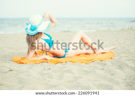 Young lady sunbathing on a beach. Beautiful woman posing at the summer sand beach. Pretty woman in blue bikini. Ocean sea coast. Beautiful fit tan girl. Sexy slim model caucasian ethnicity outdoors. - stock photo