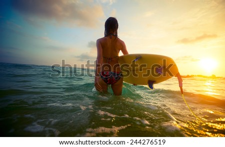 Young lady surfer walking into the sea with board - stock photo