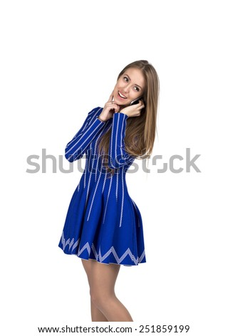 Young lady talking on the phone. Caucasian lady talking on the phone and expressing pleasure and happiness. She is in bright blue dress, smiling and cheerful. - stock photo