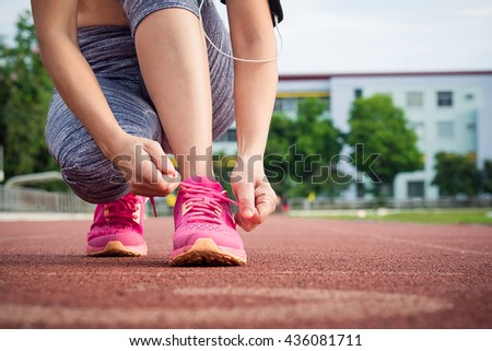 Young lady tying laces for jogging on racetrack