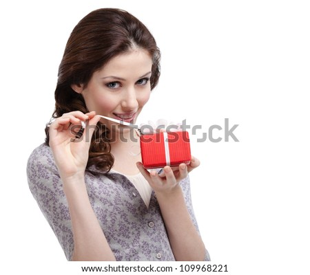 Young lady unwraps her present, isolated on white - stock photo