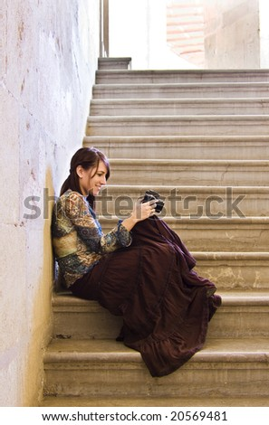 Young lady viewing her recent pictures in digital camera.