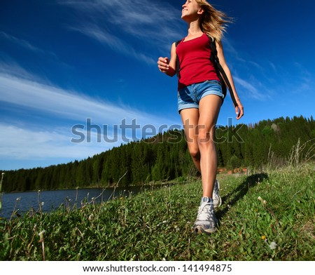 Young lady walking on a green meadow on a blue sky background