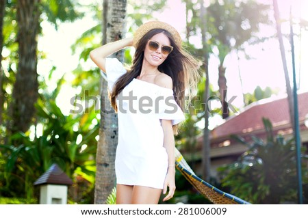 Young lady walking on the beach.Young pretty stylish sensual woman posing at amazing tropical beach with palm trees,enjoy her vacation and windy summer sunny day.Wear white dress and sunglasses.  - stock photo