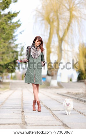Young lady walking over her puppy - stock photo