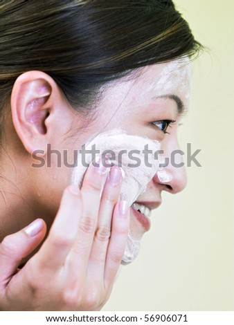young lady washing her face - stock photo