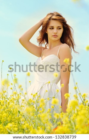 young lady wearing white dress standing in field - stock photo