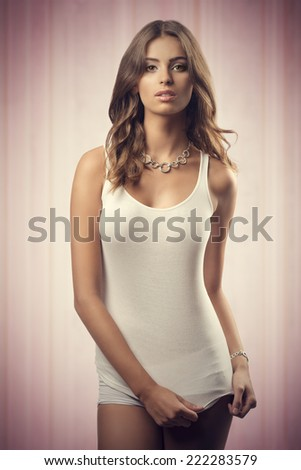 young lady wearing white undershirt and panties  and stylish necklace, in sensual pose with long natural hair  - stock photo