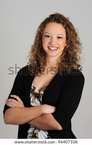 Young lady with arms folded posed on grey background - stock photo