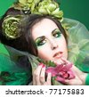 Young lady with artistic visage and with flowers in her hands and hair - stock photo