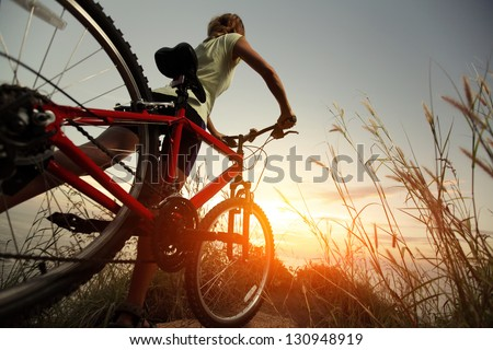 Young lady with bicycle on a rural road with grass - stock photo