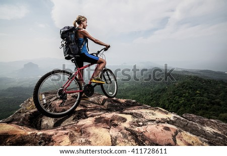 Young lady with Bicycle standing on mountain - stock photo