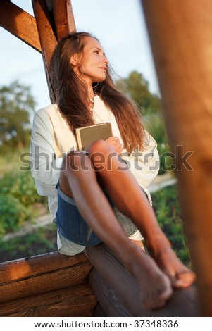 Young lady with book in summerhouse on sunset - stock photo
