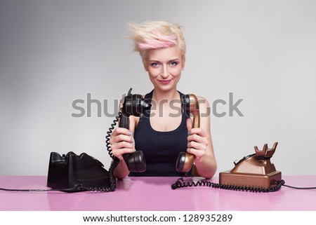 young lady with crazy hair holding handset to each other and having fun - stock photo