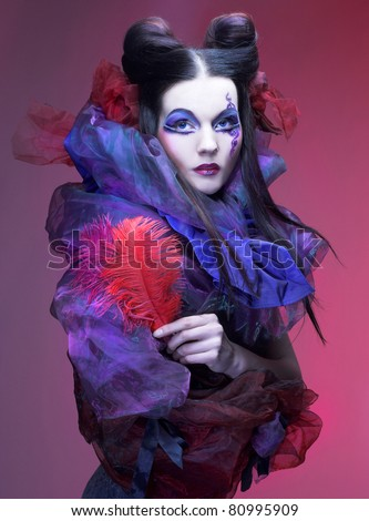 Young lady with creative visage and with feathers in her hands - stock photo