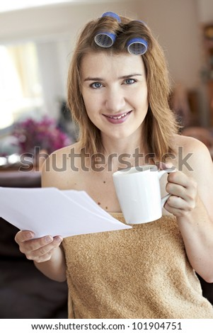 Young lady with curlers in hair while reading from notes and drinking from mug