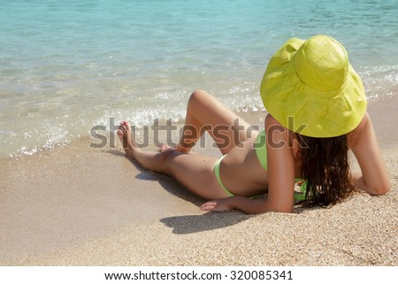 Young lady with hat on a sandy beach