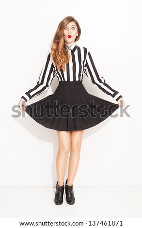 young lady with lined black and white shirt and pleated black skirt posing on white background - stock photo