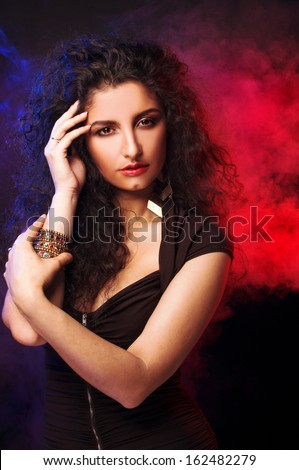 Young lady with long dark hair posing in smoke