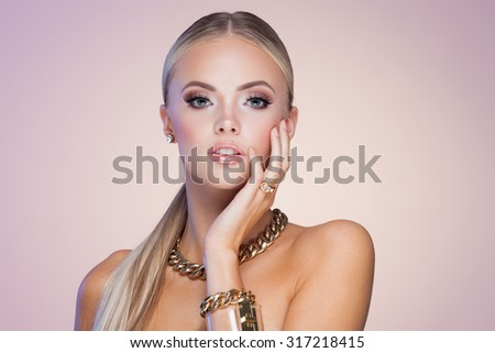 Young lady with luxury accessories on beige background - stock photo