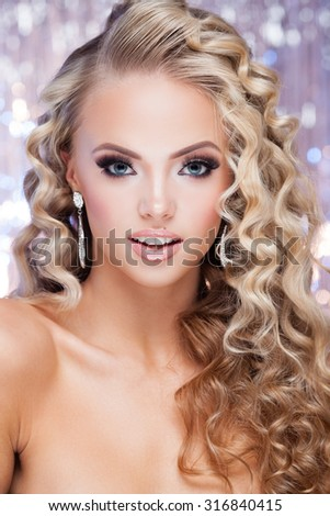 Young lady with luxury accessories on sparkling background - stock photo