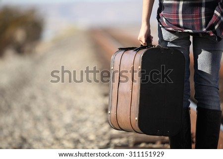 young lady with retro suitcase on railway