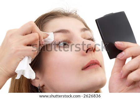 young lady with small mirror in her hand, removing makeup - stock photo