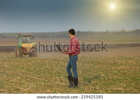 Young landowner with laptop supervising fertilizing work on farmland - stock photo