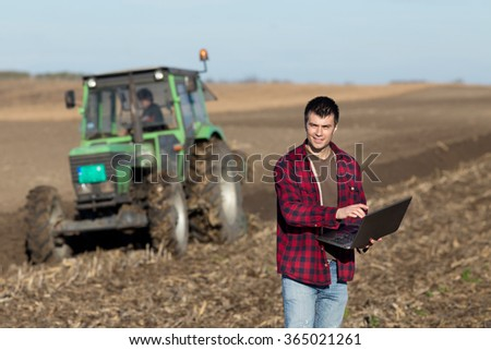 Young landowner with laptop supervising work on farmland, tractor plowing in background - stock photo