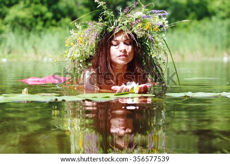 young lass with a wild flowers wreath like a nymph in a forest lake - stock photo