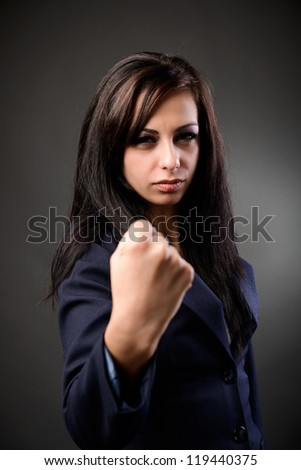 Young latin businesswoman showing her fist with a combative attitude - stock photo