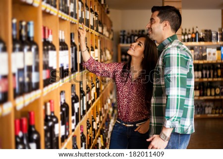Young Latin couple deciding which wine to buy at the supermarket - stock photo